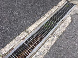 屋外で檻の様な鉄柵の蓋がしてある溝を排水溝と呼びます